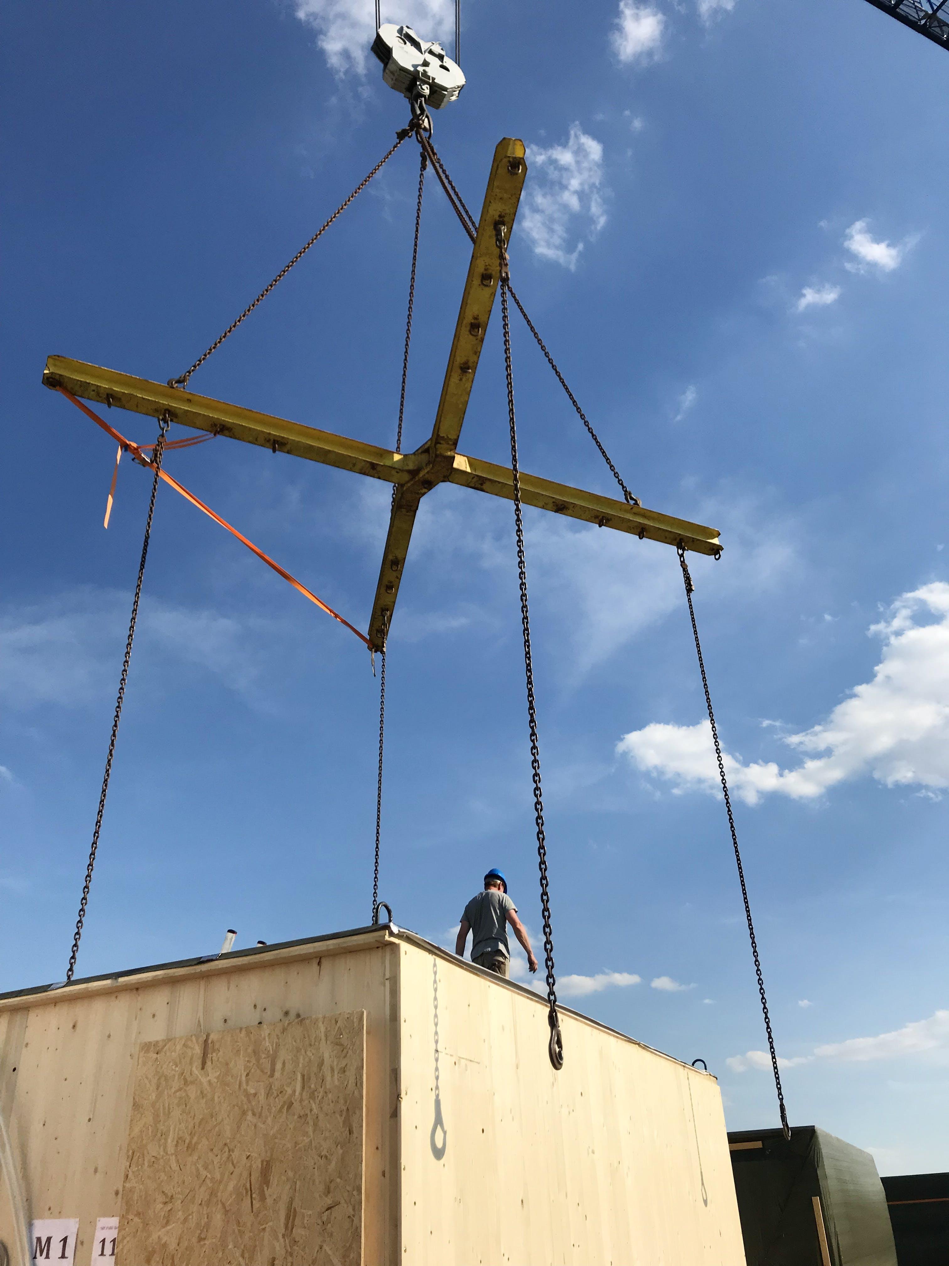 Modulbau aus Holz hängt an Kran