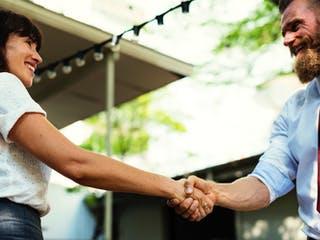 Frau schüttelt Hausbauberater die Hand