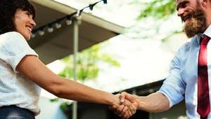 Zwei Menschen gehen einen Deal ein und geben sich freudig die Hand