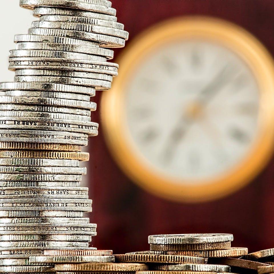 Geldmünzen vor einer Uhr
