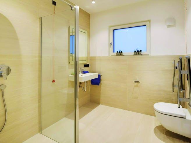 Bad mit bodengleicher Dusche und WC mit Stützgriffen