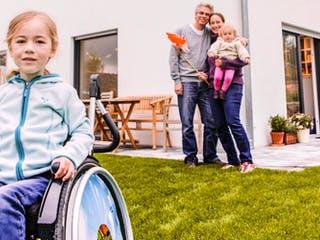 Mädchen im Rollstuhl mit ihren Eltern vor ihrem Haus
