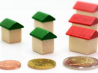 Verschieden große Holzhäuser mit unterschiedlichen Euromünzen