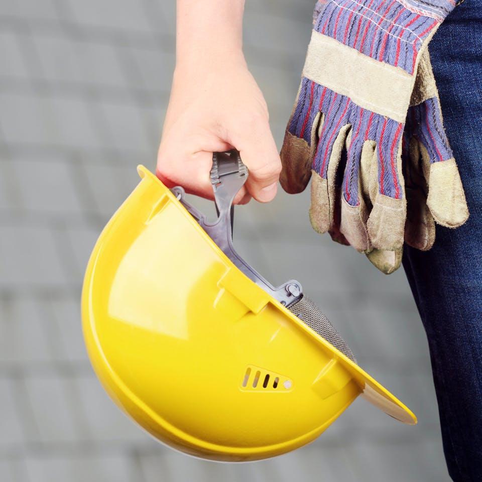 Gelber Bauhelm wird vom Bauherr in der Hand gehalten