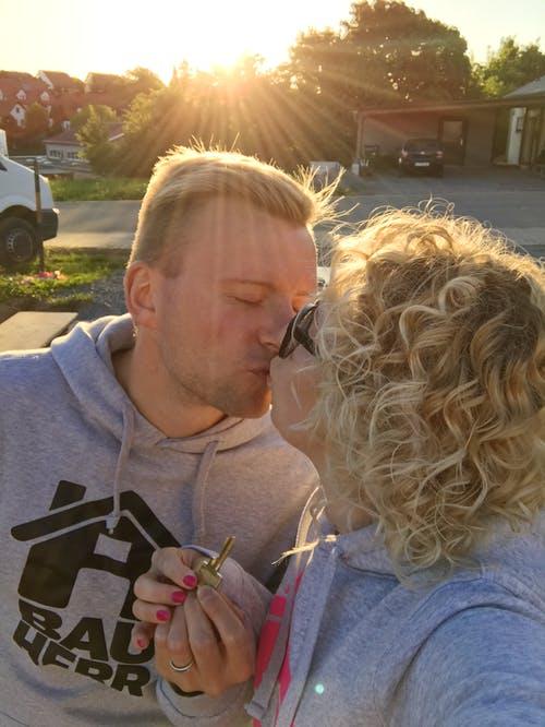 Küssendes Bauherrenpaar mit Schlüssel zum neuen Haus