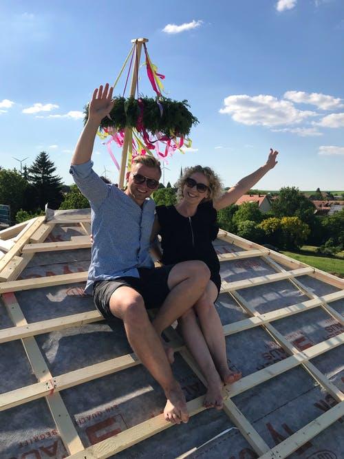Bauherrenpaar-auf-dem-Dachstuhl-unter-Richtkranz.JPEG