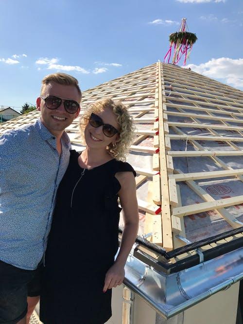 Bauherrenpaar steht auf dem Dachstuhl mit Richtkranz
