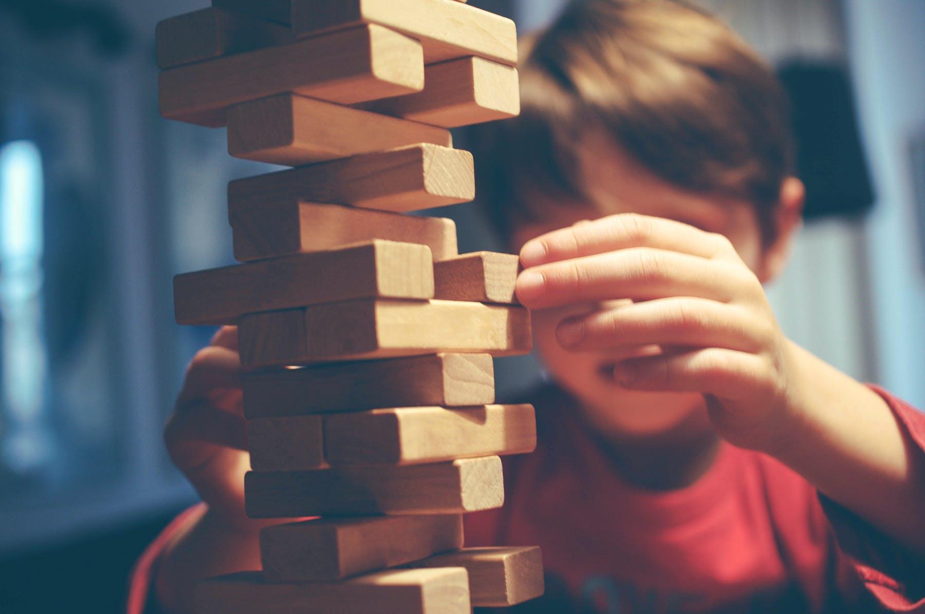 Junge baut Turm aus Holzbausteinen Jenga