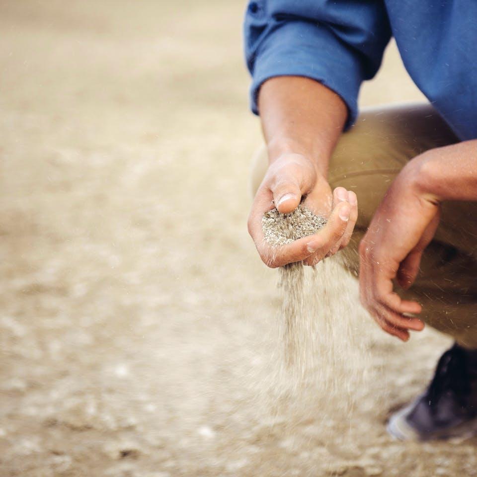 Mann prüft den Sandboden auf Eignung für Hausbau