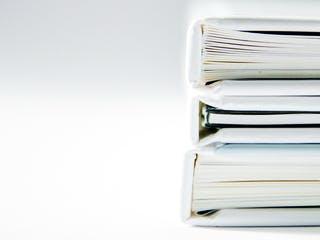 Drei weiße Bücher liegen übereinander