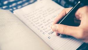 Person schreibt eine Checkliste im Notizbuch