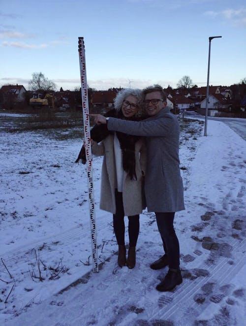 Ein Pärchen steht auf ihrem freien Grundstück mit Schnee