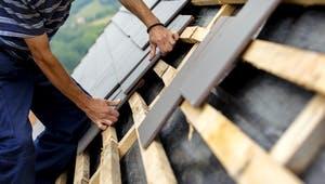 Dach wird von einem Dachdecker mit Ziegeln eingedeckt