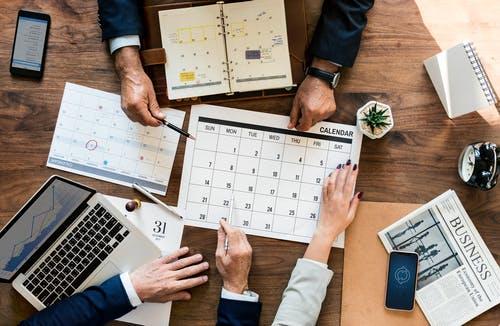 Drei Menschen planen Hausbau am Schreibtisch mit Kalender