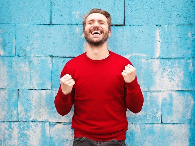Mann in rotem Pullover steht vor einer blauen Wand und freut sich