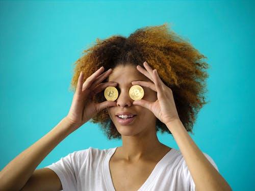 Frau hält sich die Augen mit zwei goldenen Münzen zu