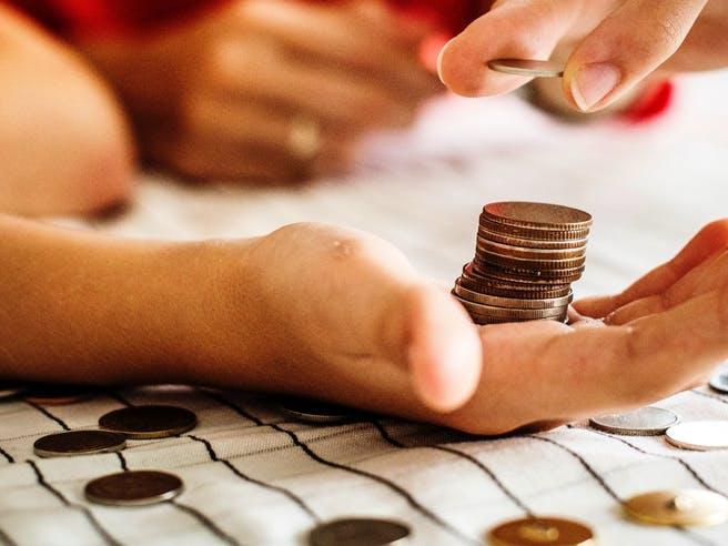 Münzen werden in einer Hand gestapelt um Geld zu zählen