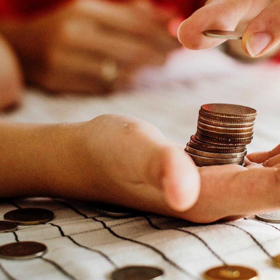 Zwei Hände im Fokus wie sie Münzen zählen