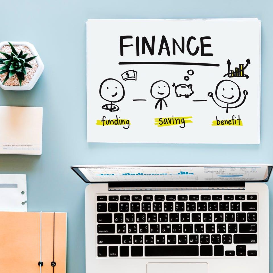 Finanzierungsplanung am Schreibtisch mit Laptop und Schreibmaterial