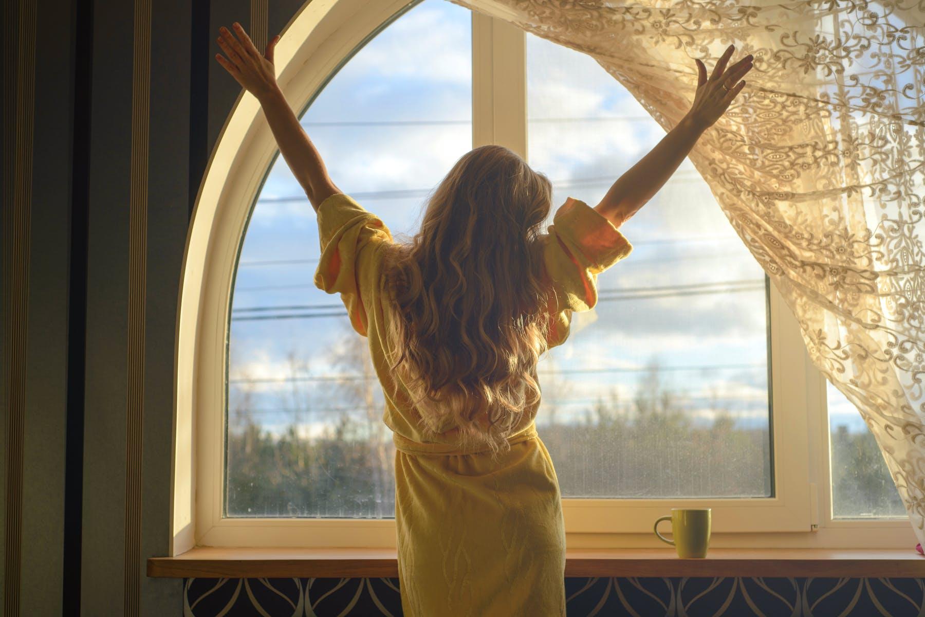 Frau streckt sich vor Fenster im Holzhaus