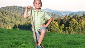 Kind mit Spaten auf einem Grundstück
