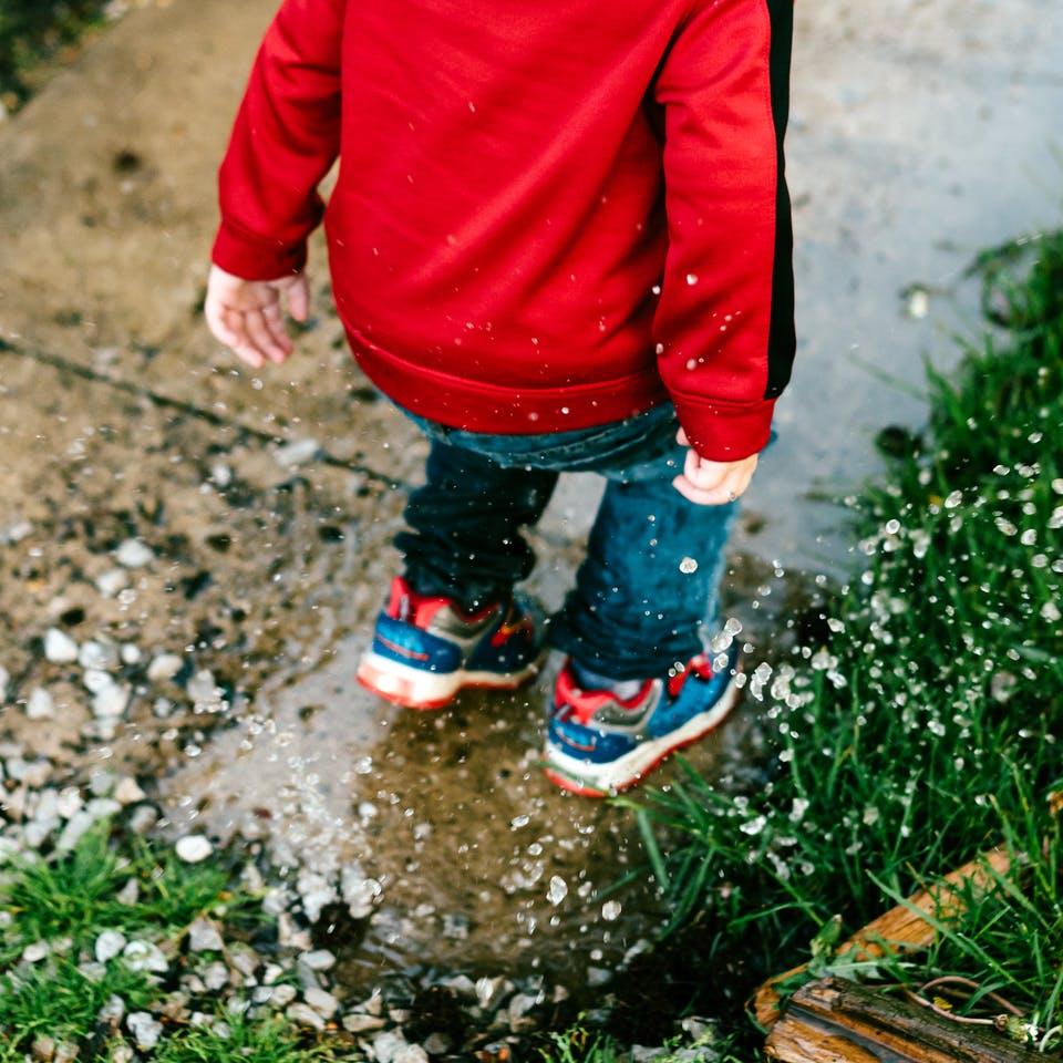 Kind springt in eine Pfütze auf dem Grundstück