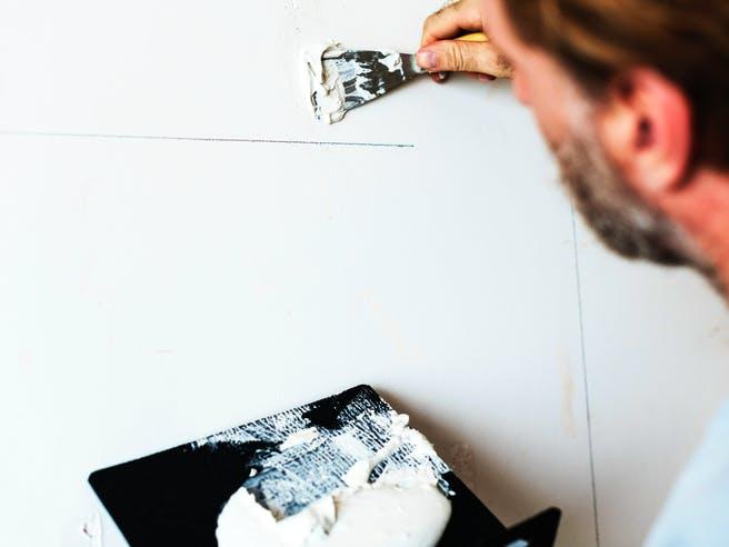Heimwerker verputzt eine Innenwand im Haus