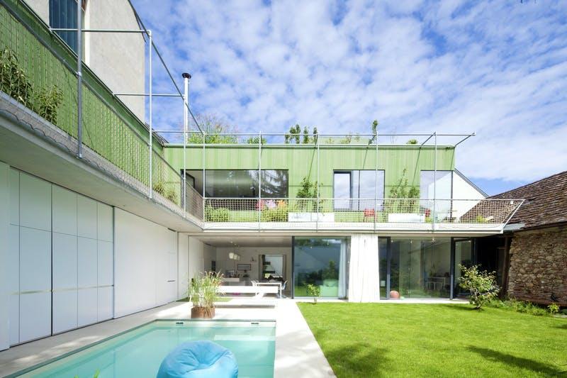 Grünes Architektenhaus mit Pool und viel Rasen