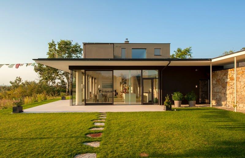 Architektenhaus mit Flachdach und großen Fensterfronten im Abendlicht