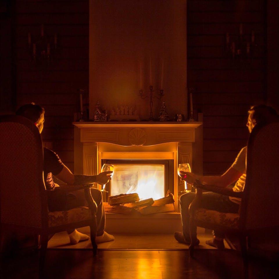 Bewohner sitzen vor Kaminfeuer im Haus