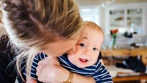 Mutter mit Baby im Arm zu Hause