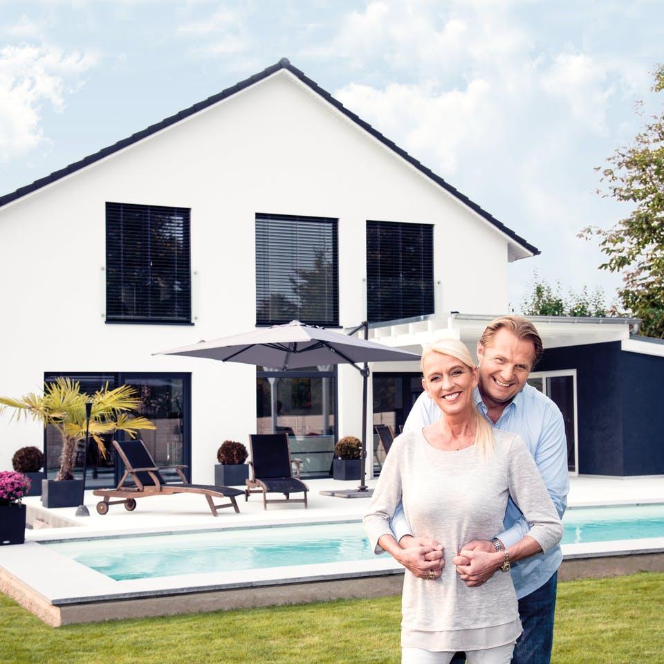 Ehepaar steht vor ihrem neugebautem Haus
