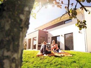 Familie sitzt im Garten vor neugebautem Haus