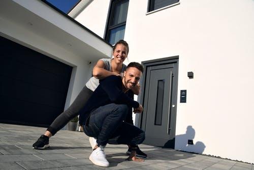 Glückliches Bauherrenpaar vor ihrem neuen Living Haus