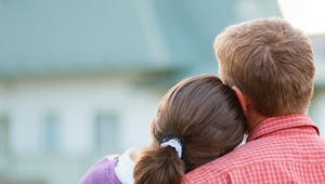 Bauherrenpaar blickt angelehnt aneinander auf ihr Haus