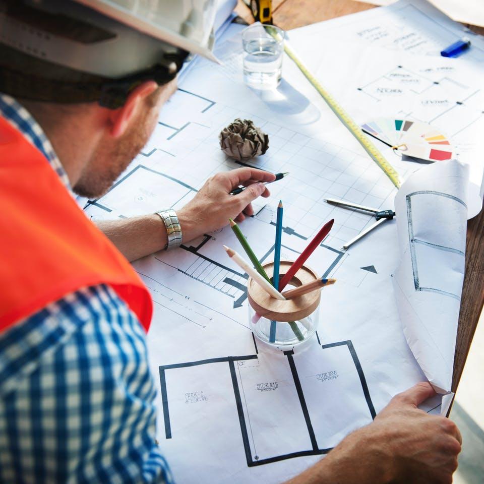 Bauherr zeichnet Grundriss für ein Haus