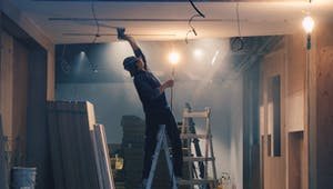 Heimwerker auf Leiter im Holzhaus