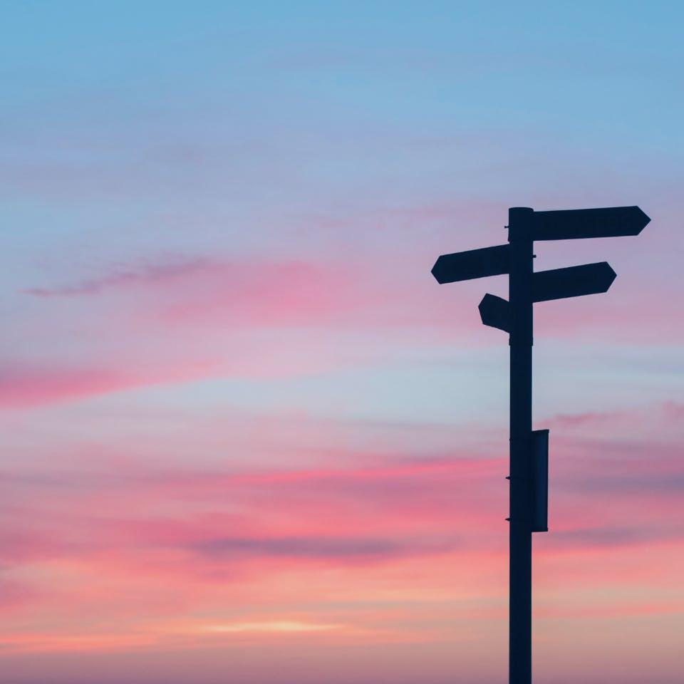 Wegweiser zeigt in verschiedene Richtungen bei Sonnenuntergang