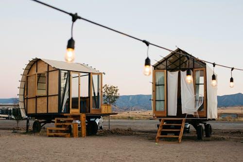 Zwei Tiny Houses aus Holz auf Rädern