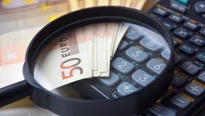 Geld mit Lupe und Rechner