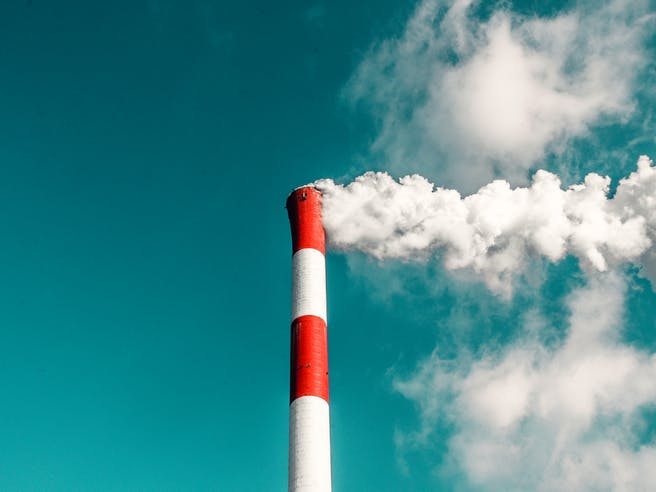 Rot weißer Schornstein einer Fabrik ragt in blauen Himmel