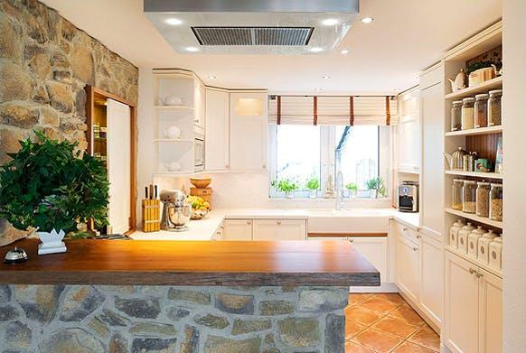 funktionale Landhausküche mit Zierelementen in weiß