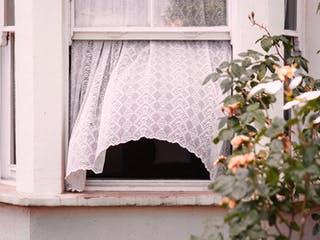 Offenes Fenster aus dem eine weiße Gardine rausweht