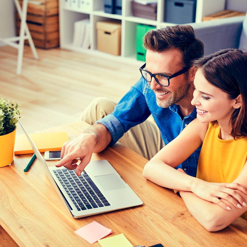 Paar bereitet sich am Laptop auf Musterhausbesuch vor