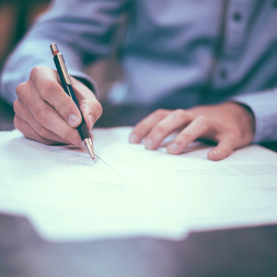 Mann unterzeichnet Kaufvertrag beim Notar