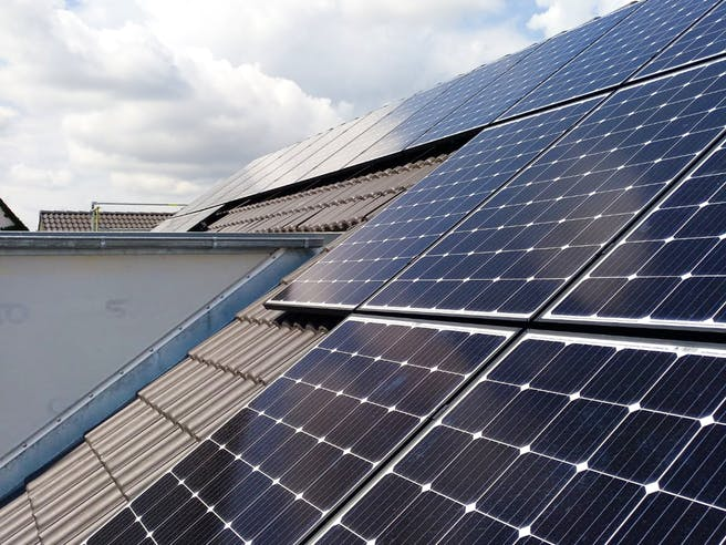 Solarkollektoren einer PV-Anlage auf dem Dach eines Einfamilienhauses