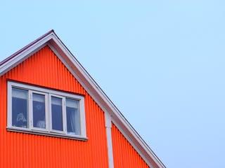 Orangenes Holzhaus mit Satteldach