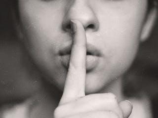 Frau hält Finger vor den Mund um Stille zu fordern
