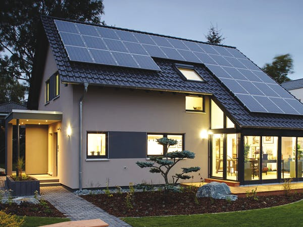 Helles Haus mit Schleppdach und Solarzellen