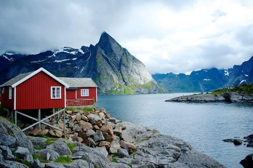 Rotes Schwedenhaus am See mit Bergen im Hintergrund